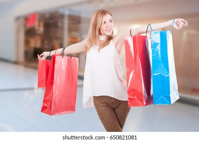 Sensual female model smiling with paper bags in the mall as shopping and consumerism concept