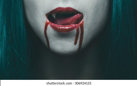 Sensual female vampire lips in blood, close-up image. Halloween or horror theme