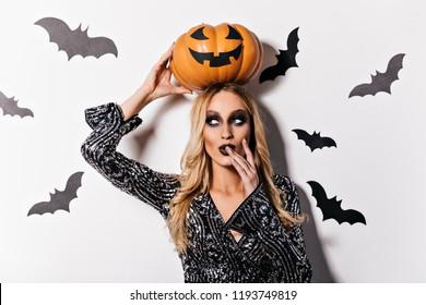 Sensual female wizard playfully posing in halloween. Indoor shot of beautiful blonde vampire.