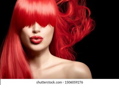 Sensual feine Kunst Schönheitsportrait einer jungen Frau mit roten Haaren mit gesunden, langen Haaren, die ihre Augen mit einem Knopf bedecken, der ihre üppigen roten Lippen mit Modelippe und Lippenstift poutiert. Einzeln auf Schwarz