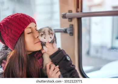 Sensual girl kissing her pet ferret on a tram on a sunny cold day. Woman and a pet concept.