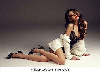 Sensual girl with long curly hair in black silk nightie, pumps and white coat sitting and posing on white background with closed eyes. Fashion vogue style portrait. Beautiful young woman.