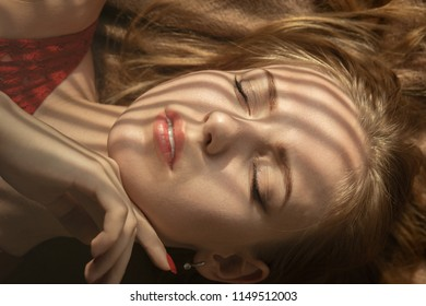 sensual girl lying on bed in sunlight with blinds shadows