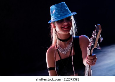 sensual girl playing on stage on a dark background as a popstar or rockstar