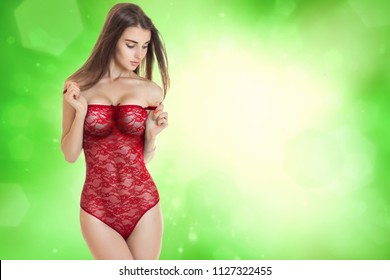 sensual girl in red lace body lingerie looking down in studio on green background