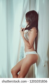 Sensual girl in underwear. Window light