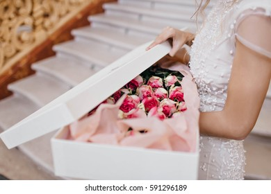 Sensual image pink roses in white box holding by young woman in white dress on stairs background. Present, gratulations, surprise, event, bride, flowers