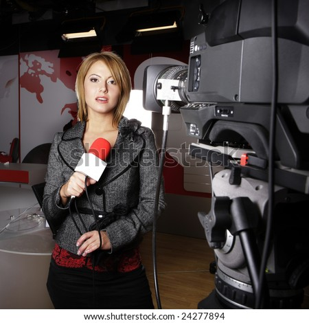 sensual journalist on the air transmitting news reports on television in front of the video camera