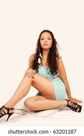 Sensual latina with beautiful long legs, seated pose on bed