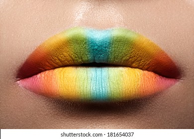 Sensual lips rainbow makeup. Beautiful bright make-up and vivid colors. Close up photography of sexy female mouth with funny summer visage