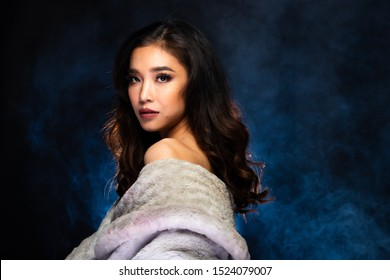 Sensual Look of Fashion Model High Make Up curl style hair Red Lips, Woman wear Fur and look at camera in beauty shot, studio lighting dark fog smoke background backlit light