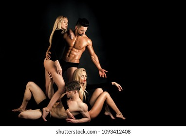 Sensual love game. Couple in love. Men with muscular body and twins, relations. men and twins women on black background, copy space
