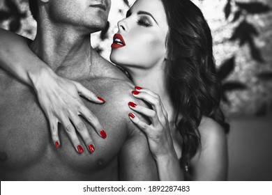 Sensual lustful woman with red lips embrace sexy man body at night, lovers, black and white selective coloring