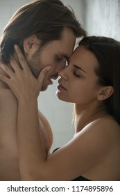 Sensual millennial couple passionately kissing near wall, woman caress lover feeling desire and temptation, boyfriend and girlfriend enjoy hot foreplay before sex, spouses having intimacy