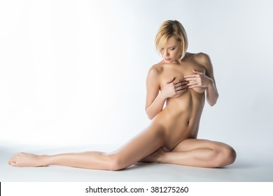 Rubia sensual desnuda posando cubriendo sus senos