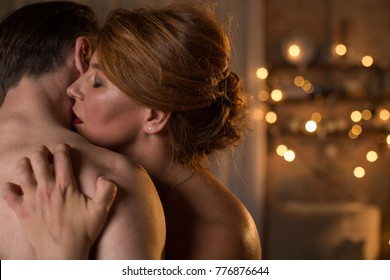 Sensual naked lovers are cuddling with passion. Female eyes are closed with pleasure. Couple is standing at bedroom in romantic atmosphere. Copy space