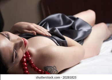 Sensual naked young Black haired adult Caucasian woman, wrapped in a charcoal colored satin, silk sheet on a bed in her bedroom. High contrast lighting.