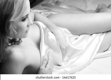 Sensual naked young blonde adult Caucasian woman, wrapped in a satin, silk sheet on a bed in her bedroom. High contrast lighting in Black and White