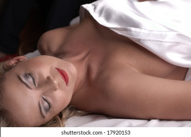 Sensual naked young blonde adult Caucasian woman, wrapped in a satin, silk sheet on a bed in her bedroom. High contrast lighting.