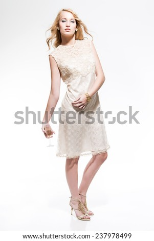 6a5e1859d06 Sensual new year s eve fashion woman with blonde hair wearing gold dress.  Holding glass of