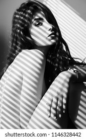 sensual nude girl sitting in sun light with blinds shadows looking at camera, monochrome