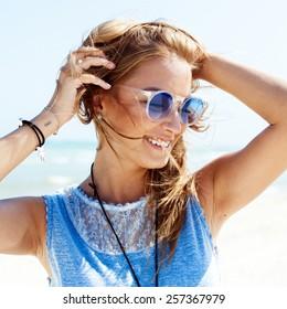 Sensual outdoor summer sunny closeup portrait of pretty young woman in sunglasses