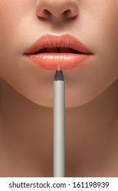 A sensual picture of woman lower face with makeup pencil in front of lips.