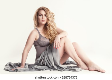 Sensual plus-size model sitting on the floor in studio