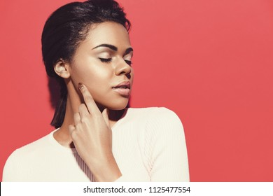 Sensual portrait of attractive African American model with perfect skin and natural make up. Skin and Face Care Concept. Posing with closed eyes against red background