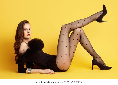 Sensual portrait of glamor brunette woman model in black body with fatin posing on yellow colorful background in studio