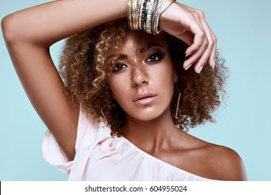 Sensual portrait of glamor elegant black hippy woman model with curly hair posing on colorful background in studio