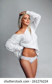 Sensual portrait of sexy blonde woman in sweater and panties over light gray background