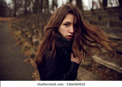 Sensual portrait shot of beautiful young girl walking in the old abandoned stadium on cold autumn day.