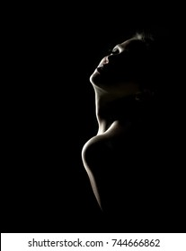 Sensual portrait of woman in shadow on dark background