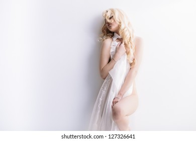 Sensual portrait of young attractive blond with transparent cloth over wall. Lot of copy space