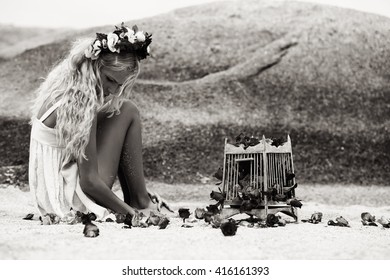 sensual portrat of beautiful blonde woman with roses and birdcage