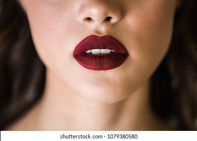 Sensual red woman lips. Half open lips. Close up face of a woman with clean skin. The concept of cosmetics, care, beauty, fashion.