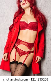 Sensual redhead woman with perfect body posing in red lingerie and cloak.
