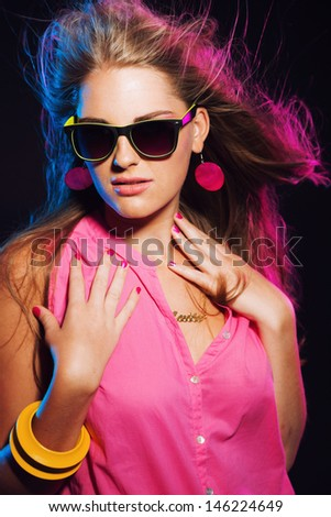 5b515fc736 Sensual retro 80s fashion disco girl with long blonde hair and sunglasses.  Black background.