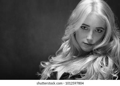 sensual sad blond woman with freckles portrait on black, monochrome