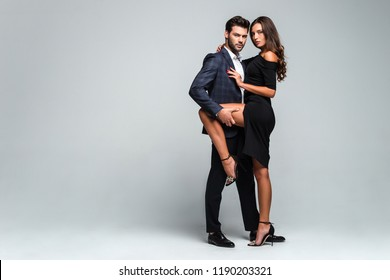 Sensual seduction. Full length of young beautiful couple bonding and looking at camera while standing against white background