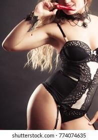 Sensual seductive attractive woman wearing sexy black lingerie holding chilli pepper. Erotic fashion concept.
