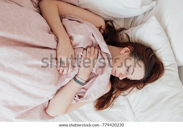 Sensual and sensitive young beautiful sexy model, attractive woman lays in bed with pink sheets on early sunday morning, enjoys calm and comfort on lazy day out