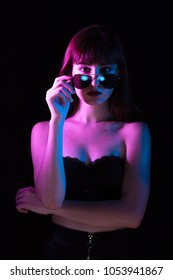 sensual serious woman with sunglasses in multicolor lights looking at camera