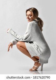 Sensual sexy long-legged vamp woman in knitted sweater on naked body and high-heeled shoes sits squatted  coquettish smiling and looks down. Sexy female look and perfect body concept