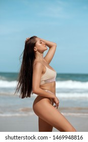 A sensual, slim lady with wet hair wearing fashion bikini and standing in the sea against the background of the waves while relaxing on the sea. Tropical vacation