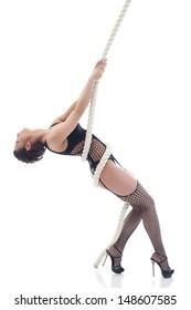 Sensual slim model suspended on rope in studio
