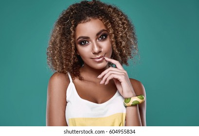 Sensual smiling portrait of glamor swag black hipster woman model with curly hair posing on colorful background in studio