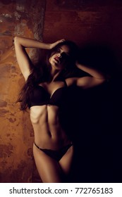Sensual tanned young woman with athletic body posing in lingerie in the shadow