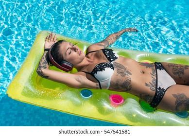Sensual tattooed woman portrait wearing bikini relaxing listening to music with earphones inside swimming pool.